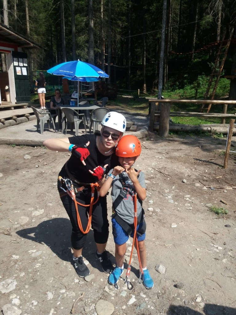 The author, a young woman, poses with a young boy while both wear climbing gear.